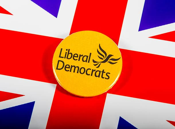 Liberal Democrat badge and a you union Jack background